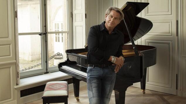 Accoudé sur un piano, Alain Lefèvre regarde la caméra.