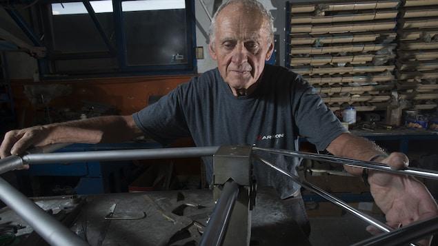 Plan rapproché de Giuseppe Marinoni en train de manipuler un cadre de vélo