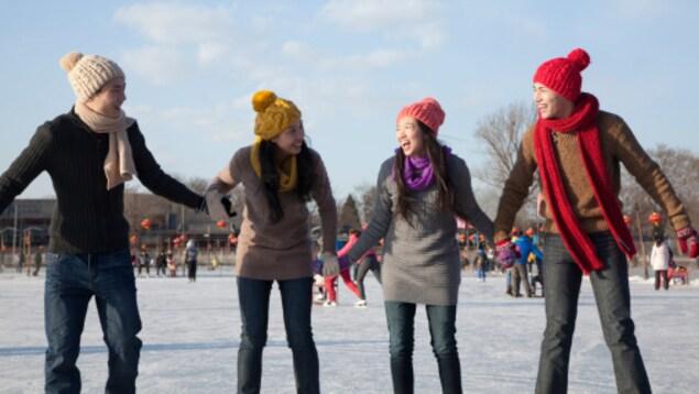 Quatre personnes se tiennent par la main sur une patinoire extérieure.