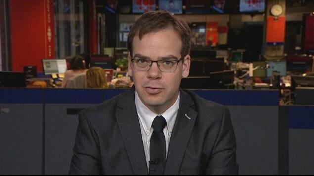 Un homme parle devant la caméra avec en arrière-plan un espace de travail ouvert et deux personnes à leur ordinateur.