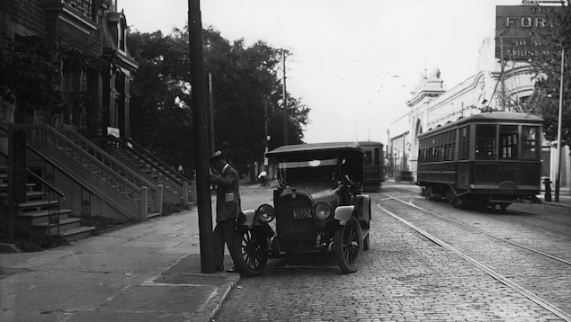 Photo en noir et blanc montrant une rue pavée sur laquelle on voit une automobile ancienne et un tramway.