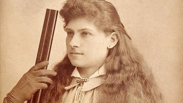 Une femme tient un fusil.