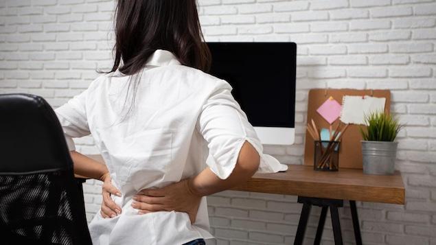 Photo d'une femme de dos, assise à un bureau, qui se touche le bas du dos.
