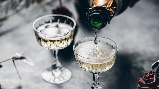 Une bouteille de bulles servie dans deux coupes de champagne.