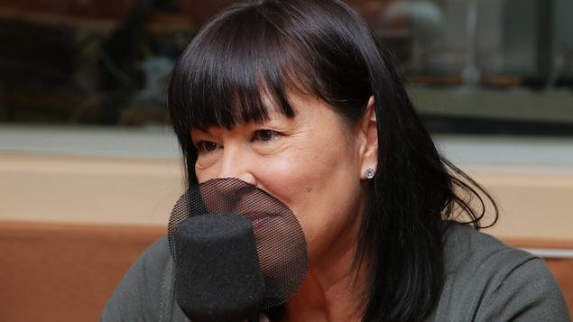 Photo de Chantal Petitclerc devant un micro de radio.