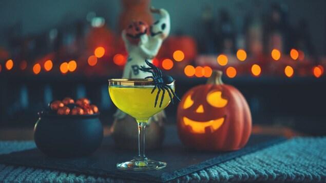 Une boisson verte servie dans un verre devant des décorations de l'Halloween (un chaudron, une citrouille et un fantôme).