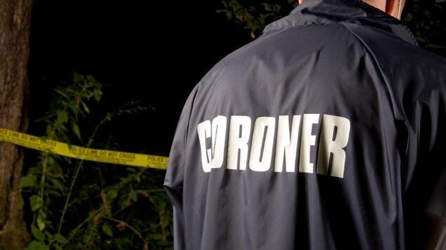 """L'inscription """"coroner"""" inscrite au dos d'une veste portée par un homme devant une scène de crime."""