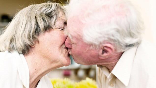 Une femme et un homme aînés se donnent un bisou sur la bouche.