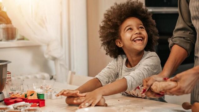 Une petite fille tient un rouleau à pâtisserie et fait un grand sourire à sa maman qui cuisine avec elle.