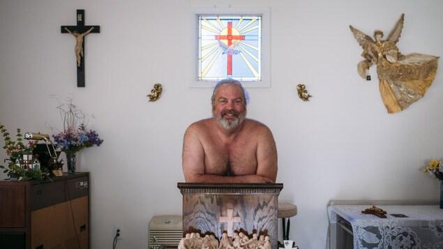Photo d'un homme torse nu derrière un pupitre dans une petite église.