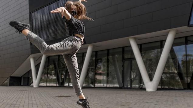 Une danseuse de danse moderne danse à l'extérieur d'un bâtiment en portant un masque.
