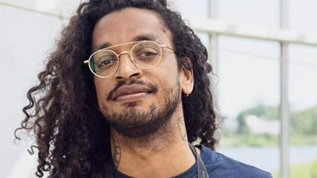 Photo d'un homme qui pose avec un tablier dans une serre.