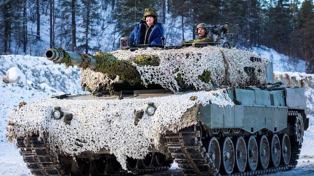 Un homme et une femme dans un char militaire sur une route enneigée.