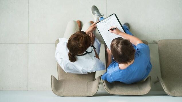 Vue aérienne de deux soignants assis sur des chaises qui remplissent ensemble un formulaire médical.