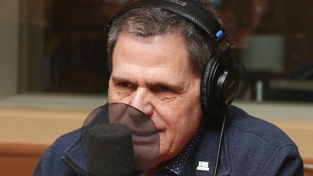Érick Rémy devant un micro de radio.