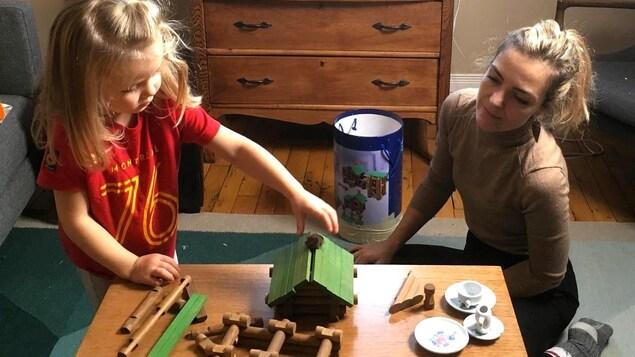Photo d'Evelyne et de sa fille dans un salon en train de jouer à construire une cabane en bois sur une table basse.