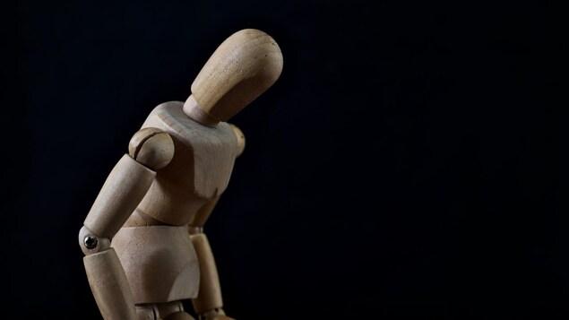La figurine de bois a le dos courbé et la tête penchée en avant.