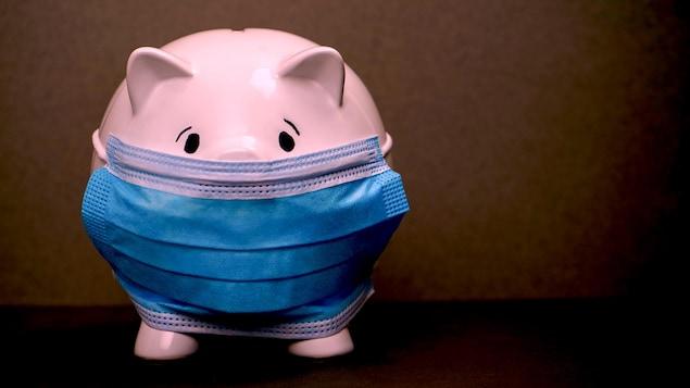 Une tirelire-cochon qui porte un masque respiratoire.