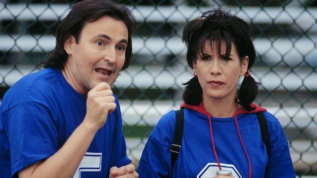 Dans une scène de la série <i>Un gars, une fille</i>, Guy A. Lepage et Sylvie Léonard sont habillés en joueurs de baseball devant un grillage.