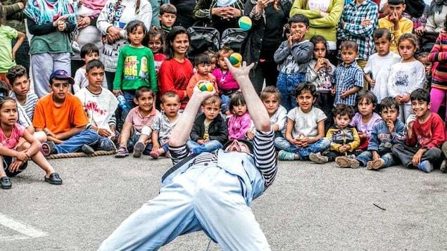 Guillaume Vermette, déguisé en clown, jongle devant des enfants et des adultes réunis autour de lui.