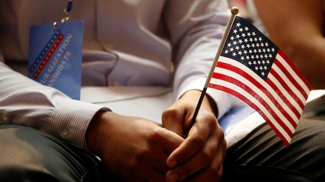 Gros plan sur les mains d'un homme qui tiennent un petit drapeau américain.