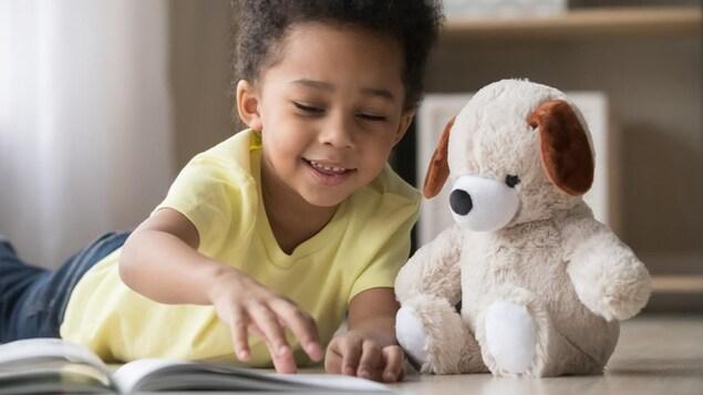 Un jeune garçon lit un livre allongé avec un toutou.