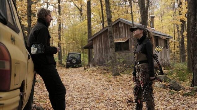 Emmanuel Schwartz se tient contre une voiture et parle à Sarah-Jeanne Labrosse, qui est en habit de chasse, dans une forêt.