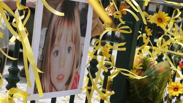 Une photo d'une petite fille accrochée à une barrière avec des fleurs et des rubans.