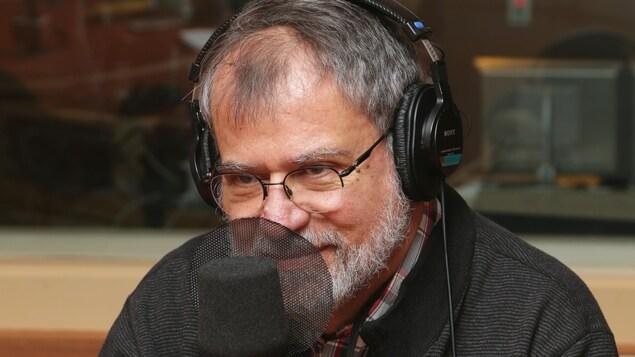 Photo de Martin Winckler devant un micro de radio.