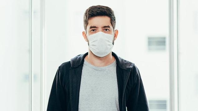 Un homme porte un masque à l'intérieur.