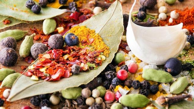 Feuilles de laurier, grains de poivre, flocons de piment, graines fenouil, coriandre en grain, clous de girofles étalés sur une table.