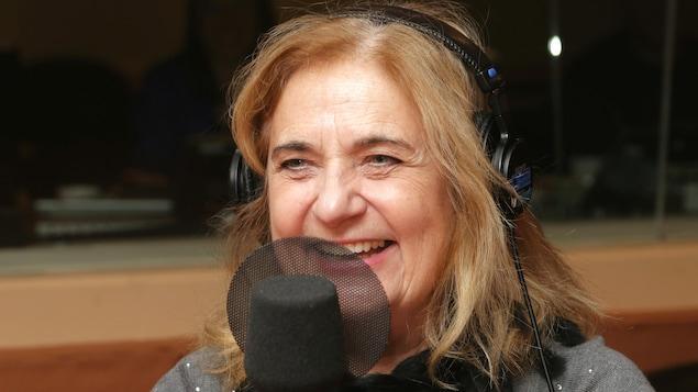 Photo de Nathalie Petrowski devant un micro de radio.