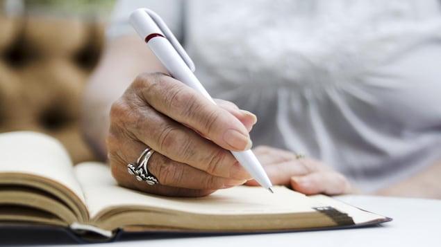 La main d'une femme âgée tient un stylo et s'apprête à écrire dans un carnet.