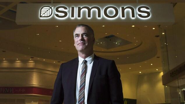 Il pose devant l'enseigne lumineuse d'un magasin Simons.