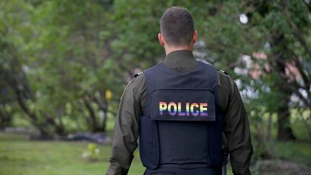 """Un policier de dos porte un gilet pare-balles avec l'inscription """"Police"""" inscrite aux couleurs du drapeau arc-en-ciel."""