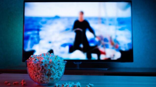 Un bol de maïs soufflé devant une télé allumée floue en arrière plan.