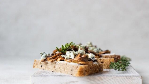 Des tartines de champignons et de fromage bleu disposées sur une planche en bois.