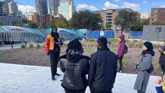L'homme parle dans un parc devant une dizaine de personnes.