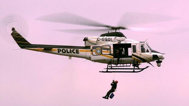 Un hélicoptère de la Sûreté du Québec, avec l'inscription « Police », vole et hélitreuille un homme.