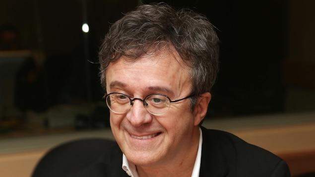 Stéphane Laporte devant un micro de radio.