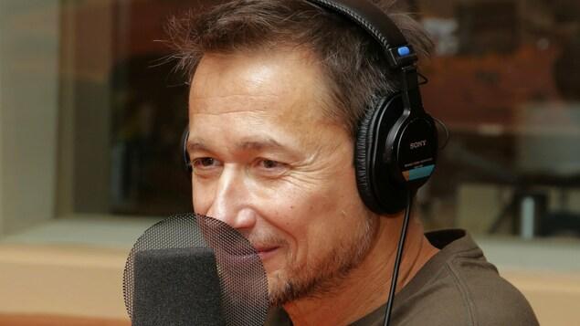 Photo de Stéphane Rousseau devant un micro de radio.