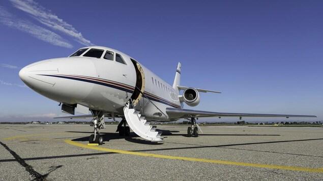 Un petit avion attend sur une piste d'aéroport.