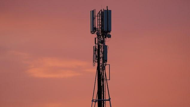 Une tour de télécommunication se découpe en contre-jour sur un ciel de coucher de soleil.