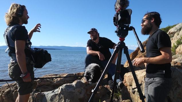 Le réalisateur et sa caméra, un preneur de son et un invité du film sur des rochers au bord du fleuve.