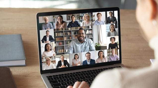 Une personne devant son ordinateur portable sur l'écran duquel s'affichent une vingtaine de personnes.