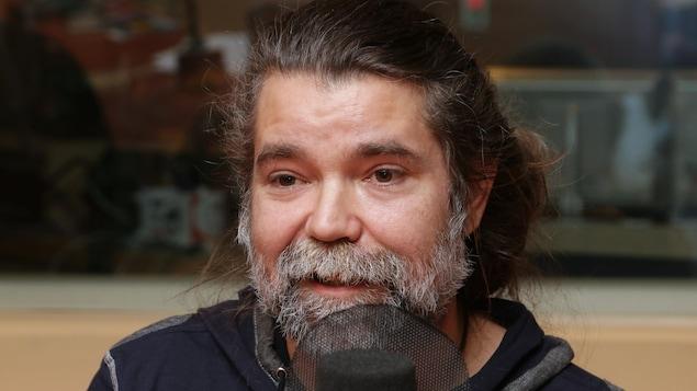 Photo de Yan Défossés devant un micro de radio.