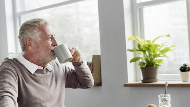 Un homme âgé en train de boire dans une tasse en regardant par la fenêtre.