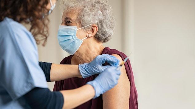 Une patiente âgée est masquée alors qu'un médecin prépare une injection.