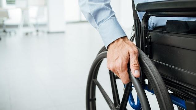 La main d'une personne en fauteuil roulant posée sur la roue.
