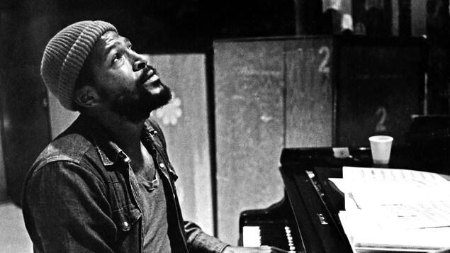 Photo en noir et blanc d'un homme qui joue du piano en regardant en l'air.